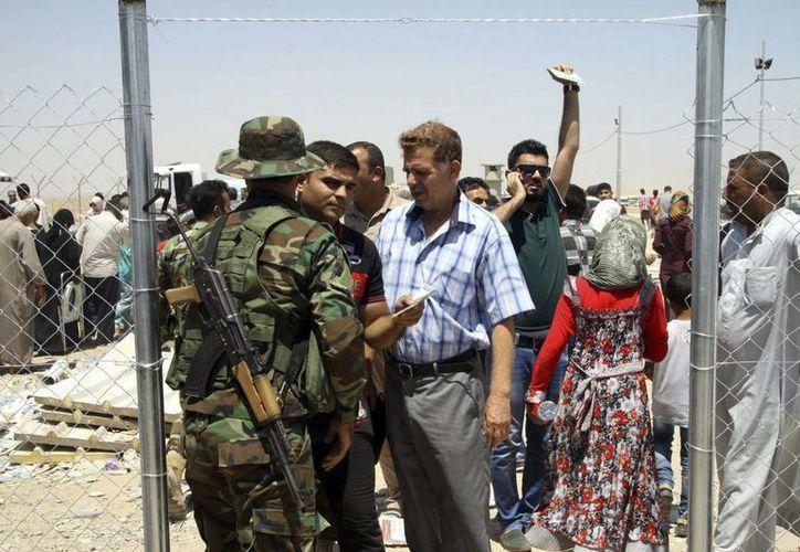 Varios soldados comprueban la documentación de varios iraquíes, que huyeron de la violencia en Mosul. (EFE)