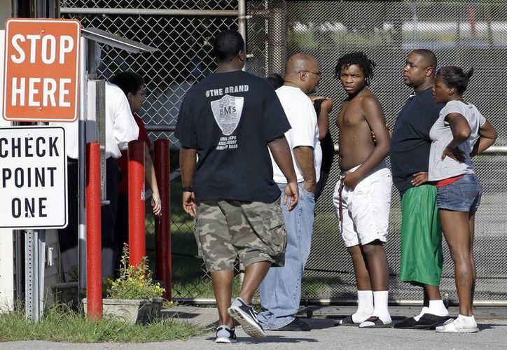 Uno de los adolescentes que escaparon (tercero desde la derecha), es devuelto por su familia, a la entrada del Centro de Desarrollo Juvenil Woodland Hills, en Nashville, Tennessee. (Agencias)