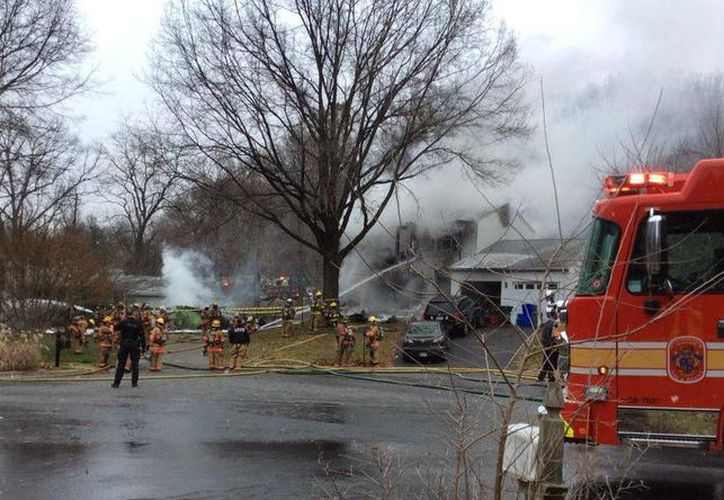 La casa donde se estrelló la avioneta se envolvió en llamas junto con otras dos viviendas. (Twitter/@PzFeed)