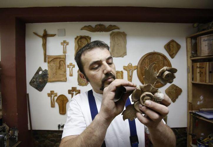 Edin Hajdarovac trabaja en una decoración que forma parte de la silla de madera que el Papa Francisco utilizará en junio durante su visita a Bosnia. (Agencias)