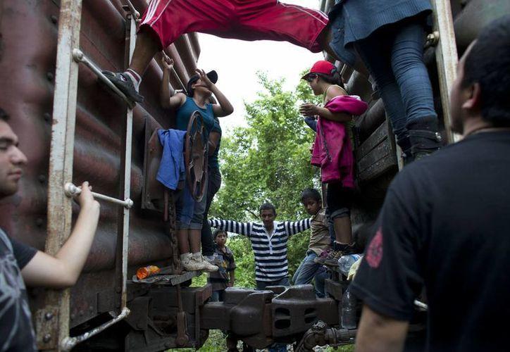 Inmigrantes centroamericanos colgados de un tren con rumbo al norte en el que viajaban, después de un leve descarrilamiento en una remota zona boscosa en Reforma de Pineda, Chiapas. (Agencias)