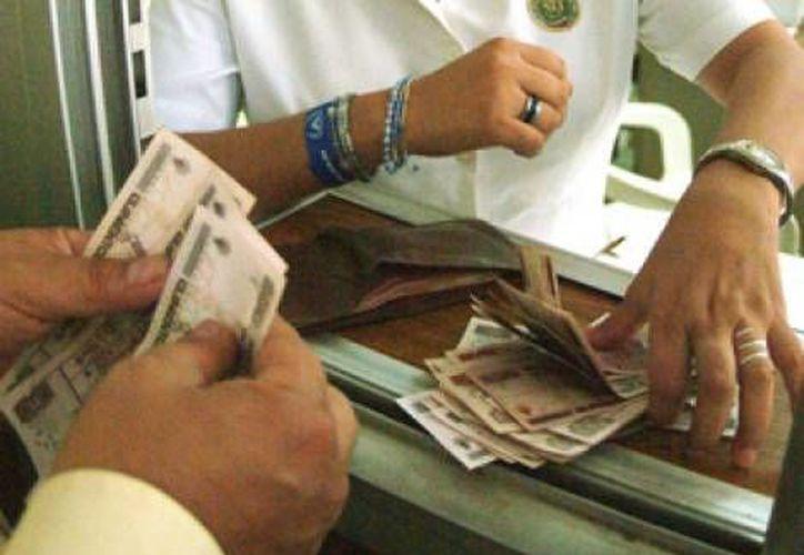 En bancos y casas de cambio, el dólar llegó a comprarse en 11.70 pesos. (MILENIO)