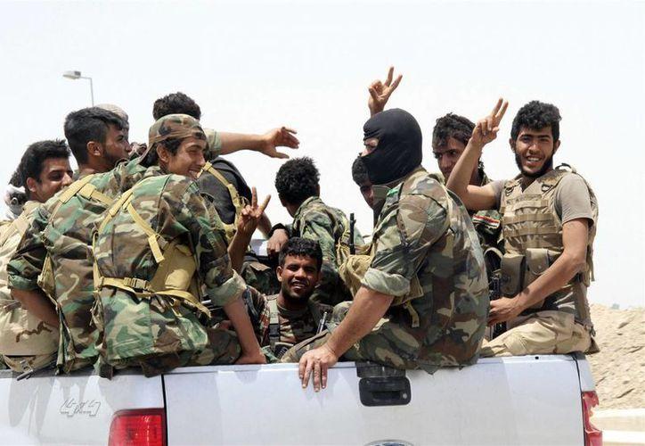 Imagen de milicianos chiíes al llegar a Jalidiya para apoyar a los tribales suníes y policías locales que defienden su ciudad contra combatientes del grupo Estado Islámico. (AP Foto)