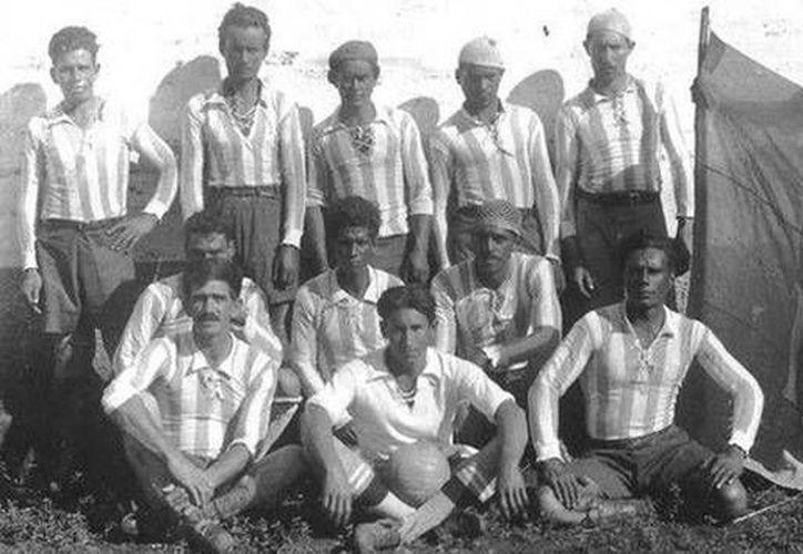 Un equipo de fútbol posa para una fotografía conmemorativa junto a la enorme esvástica de la bandera que sostiene uno de los jugadores. (bomlero.blogspot.ru/ Senhorinha Barreto da Silva)