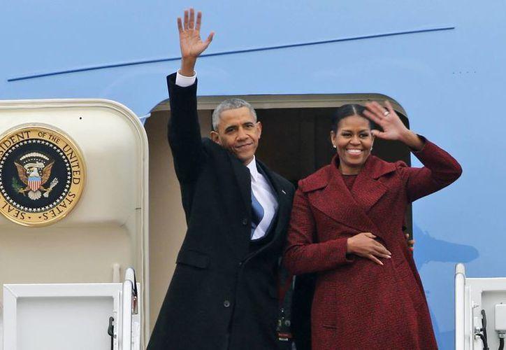El ahora expresidente Barack Obama y su esposa Michelle saludan a la multitud antes de abordar un avión de la Fuerza Aérea para abandonar la base de Andrews en, Maryland. (AP Photo / Steve Helber)