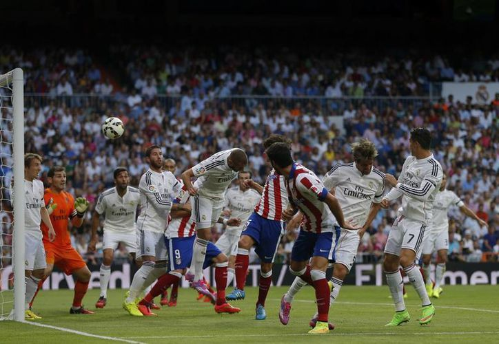 Con este remate seco de cabeza, Tiago (c) puso en ventaja al Atlético en casa del Real Madrid. (Fotos: AP)