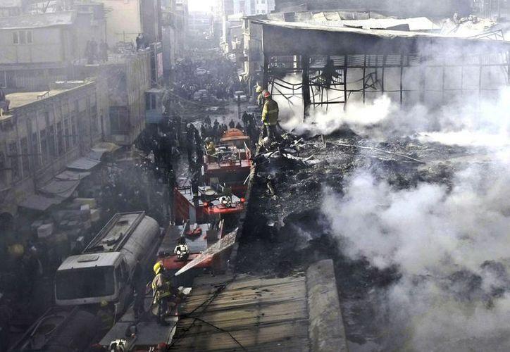 Los bomberos tardaron varias horas en apagar el incendio. Muchas personas trataron de salvar sus mercancías, sin conseguirlo. (Agencias)