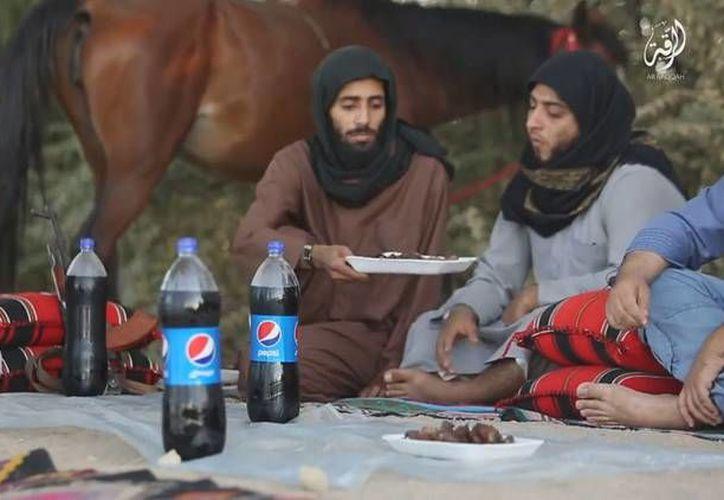 En algunos videos, los yihadistas aparecen sentados frente a una comida de platos de plástico y bebidas Pepsi, como si se tratase de un pícnic. (Captura de pantalla de un video propagandístico del EI)