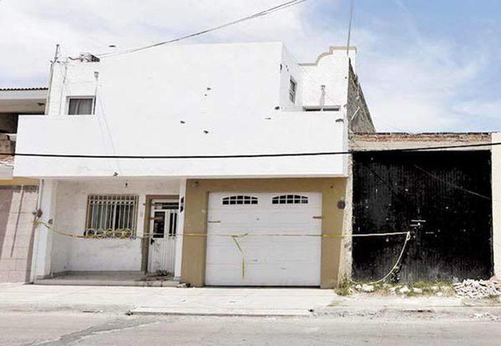 Una casa asegurada en donde se ven marcas de proyectiles. (Alejandro Acosta/Milenio)