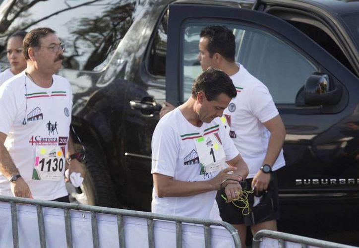 El presidente Enrique Peña Nieto corrió 10 kilómetros en la carrera Molino del Rey, organizada por el EMP. En la imagen, el mandatario calienta motores, previo a la justa. (presidencia.gob.mx)