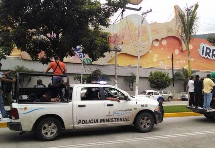 Imagen de policías ministeriales en el momento de trasladar a los agentes municipales de Iguala detenidos tras los hechos del 26 y 27 de este mes con normalistas de Ayotzinapa. (Notimex)