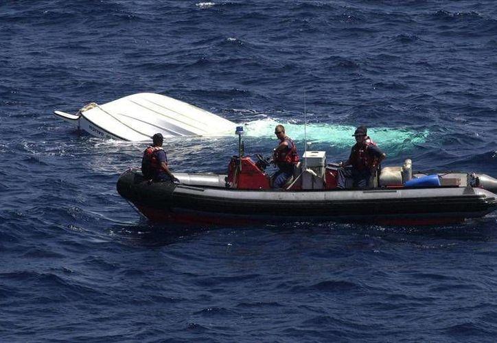 Las nueve personas que se afianzaban del casco eran haitianos y jamaiquinos. (epa)