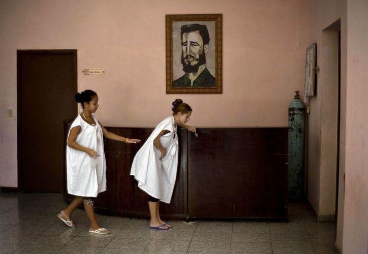 Una mujer embarazada ayuda a otra que siente dolores relacionados con el parto mientras ambas pasan junto a un retrato de Fidel Castro en una clínica especial para embarazos de alto riesgo en La Habana. (Agencias)