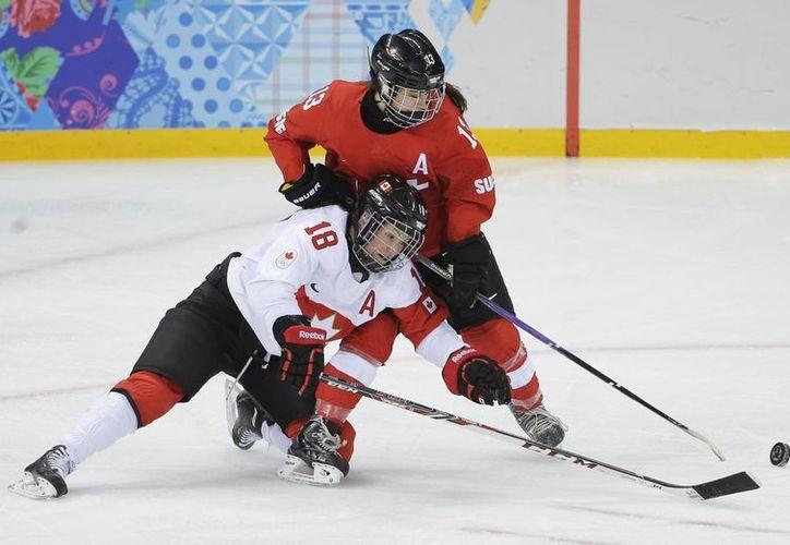 La canadiense Catherine Ward (de blanco) disputa con la suiza Sara Benz la posesión del disco en una de las semifinales de hockey femenil en Sochi. (Agencias)