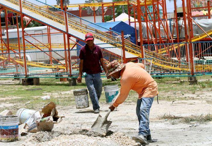 Trabajadores preparan el área en donde se ubicarán los juegos mecánicos de la feria de la Virgen del Carmen.  (Adrián Monroy/SIPSE)