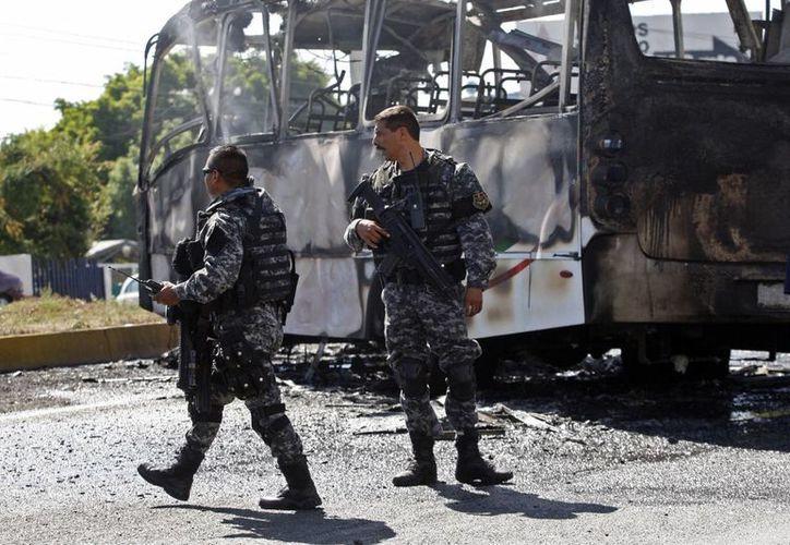 Dos agentes se encuentran junto a un autobús de pasajeros carbonizados, en Guadalajara, Jalisco. (Agencias)