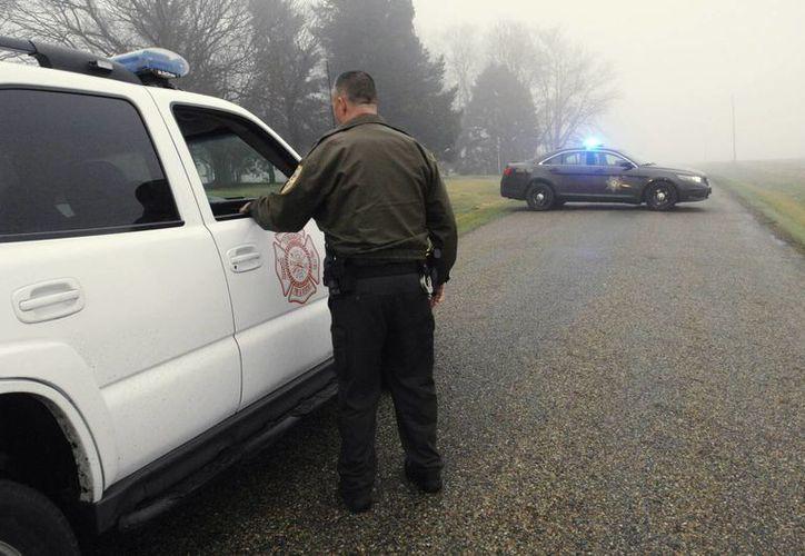 Un policia del condado de McLean vigila el lugar cerca donde se suscitó la caída de un avioneta que salió de Indiana. (AP)