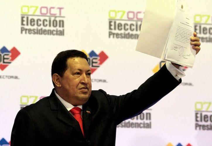 El presidente venezolano, Hugo Chávez, con el acta que certifica su triunfo en el proceso electoral de Venezuela. (Archivo Notimex)