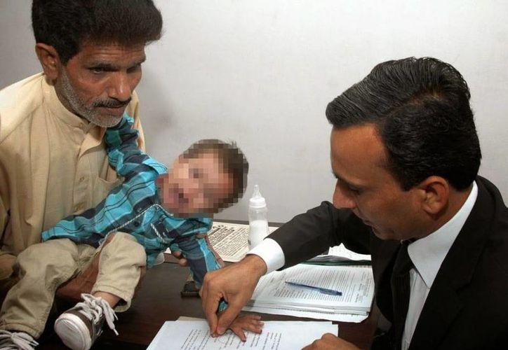 Toma de huellas del pequeño Musa Khan mientras es abrazado por un pariente suyo. (Foto: AFP/Getty Images)