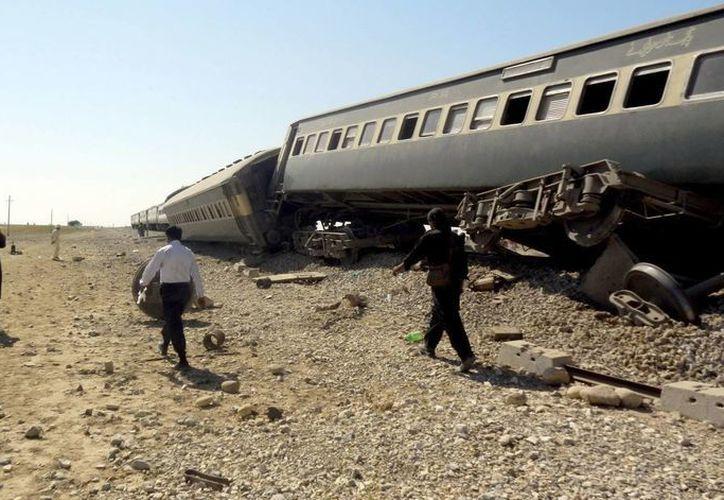 Oficiales inspeccionan el tren en el sitio de la explosión en Naseerabad. (EFE)