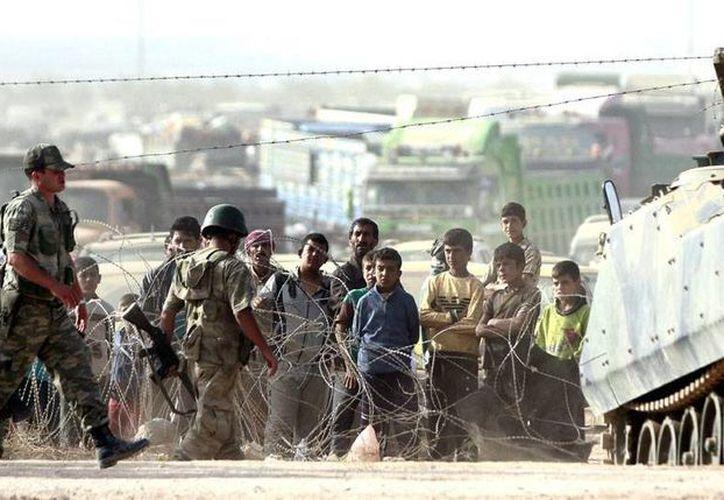 Los ataques aéreos arrecian en Siria y sus ciudadanos buscan salir a cómo dé lugar del país. En  la imagen, sirios observan los movimientos de soldados turcos en la frontera común de ambos países. La imagen es de contexto. (Efe/Archivo)