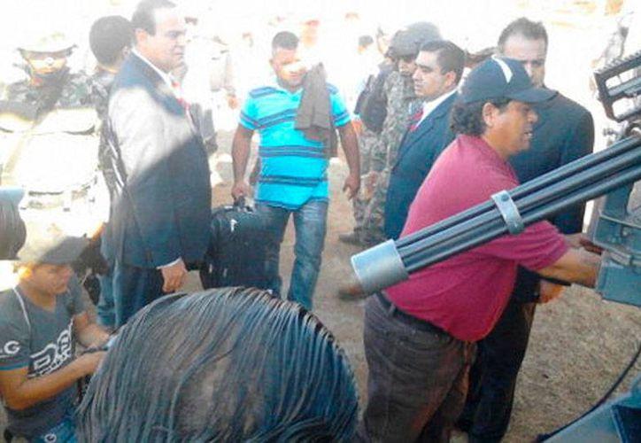 Luis Antonio Torres, alias El Americano (de playera roja), se entregó esta mañana a las autoridades Michoacán, para responder por la balacera ocurrida en La Ruana. (Milenio Digital)