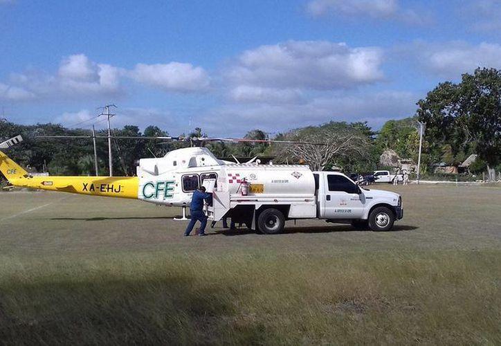 Un helicóptero de la CFE tuvo que aterrizar de emergencia en un campo de fútbol de José María Morelos, en pleno partido. (Tony Blanco/SIPSE)