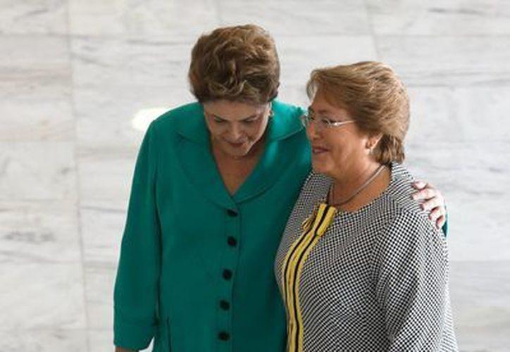 Foto de archivo de junio 12 de 2014 en la que Dilma Rousseff (i), presidenta de Brasil, da la bienvenida a su homóloga chilena Michelle Bachelet en el Palacio presidencial en Brasilia. Hoy la popularidad de ambas está prácticamente por los suelos. (Foto: AP)