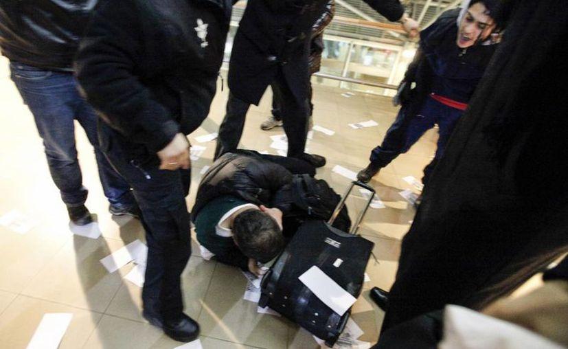 Julio Castañer, exmilitar chileno, yace en el piso mientras manifestantes lo patean y lo insultan cuando intentaba tomar un vuelo. El viernes, Castañer y otros seis exmilitares fueron acusados de la muerte por quemaduras del chileno Rodrigo Rojas, que perdió la vida en una protesta en 1986 contra la dictadura militar. (AP)