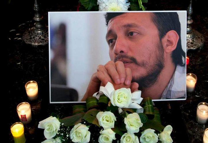 Fotografía de Rubén Espinosa, reportero gráfico asesinado en la Narvarte, entre flores y velas delante de su ataúd en la Ciudad de México. (Agencias)