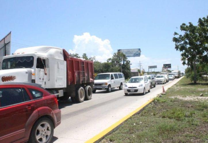 Debido al operativo de seguridad que se instaló en la carretera federal, se formaron largas filas de vehículos.  (Luis Ballesteros/SIPSE)