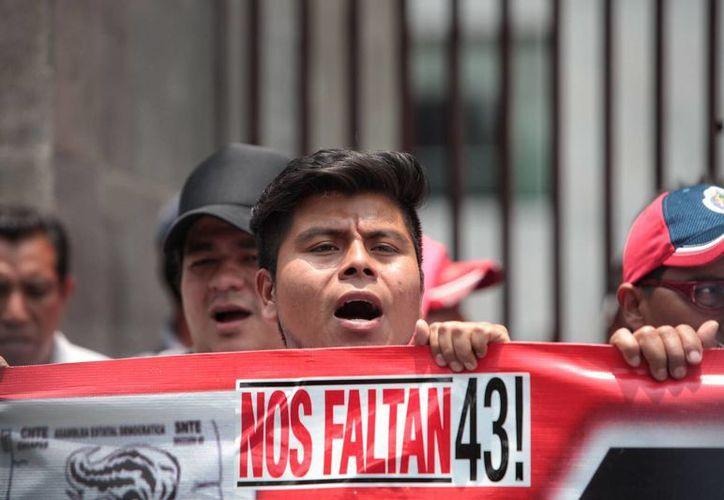 Un grupo de personas entre miembros de la Coordinadora Nacional de Trabajadores para la Educación (CNTE) y familiares protestan en apoyo a los padres de los 43 normalistas desaparecidos en Ayotzinapa . (EFE/Archivo)