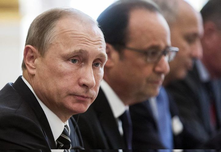El presidente ruso, Vladimir Putin (izq), y el presidente Francois Hollande (centro) asisten a una reunión con la canciller alemana Angela Merkel y el presidente ucraniano Petro Poroshenkoen (fuera de cuadro) en París. (Agencias)