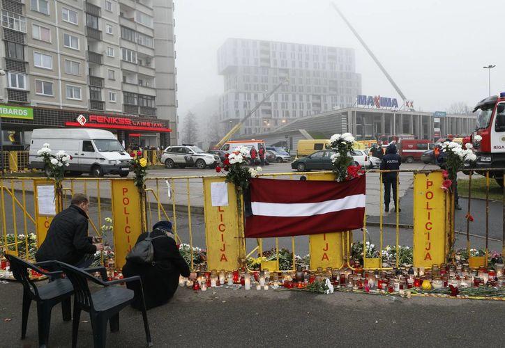 La gente pone flores y encender velas en frente del supermercado Maxima en Riga. (Agencias)