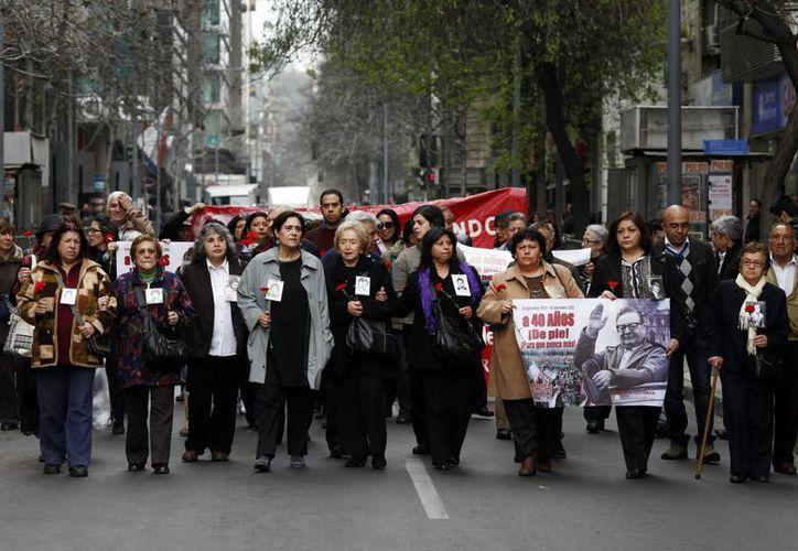 Un grupo de personas marcha hacia el monumento al expresidente Salvador Allende durante un acto en su honor en Santiago, a una semana del 40 aniversario del golpe de Estado en Chile. (EFE)