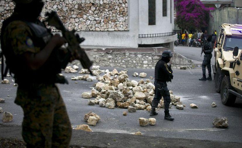 Los oficiales del palacio nacional quitan una barricada durante una protesta por las condiciones salariales y laborales, en Petion-Ville, Haití. (Foto AP / Dieu Nalio Chery)