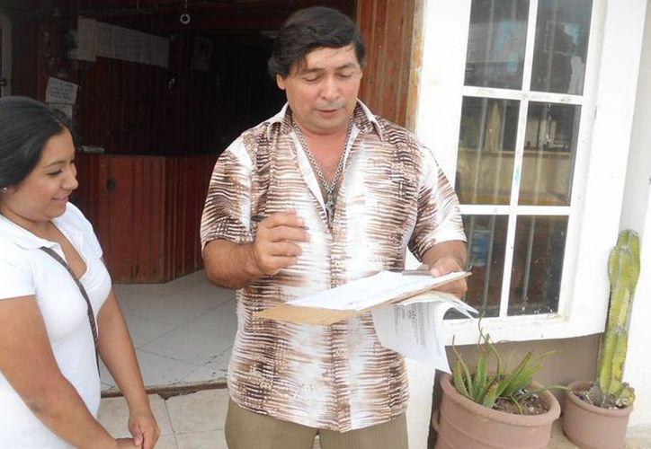 El empresario Pedro Zacarías  firma la invitación al curso sobre identidad cultural. (Manuel Pool/SIPSE)