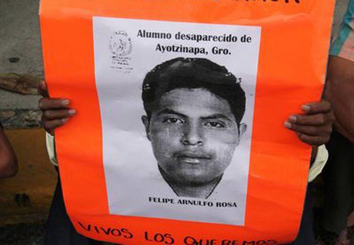 Imagen de uno de los normalistas de Ayotzinapa desaparecidos es sostenida durante una protesta que se realizó en Guerrero. (Agencias)