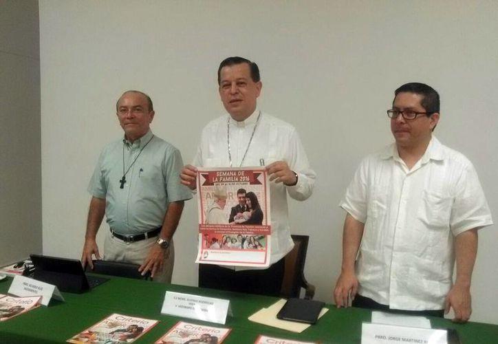 El Arzobispo de Yucatán muestra el cartel conmemorativo de la Semana de la Familia. En el lugar declaró que la llamada ideología de género amenaza a la familia.  (Milenio Novedades)
