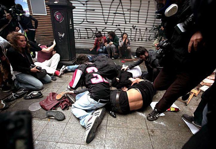 Imagen de manifestantes turcos tirados en el piso después de que la policía les lanzara gas lacrimógeno. (Agencias)