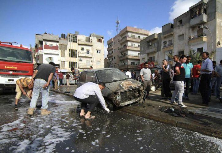Varios ciudadanos libios limpian la zona donde explotó un coche bomba en Bengasi, Libia. (Archivo/EFE)