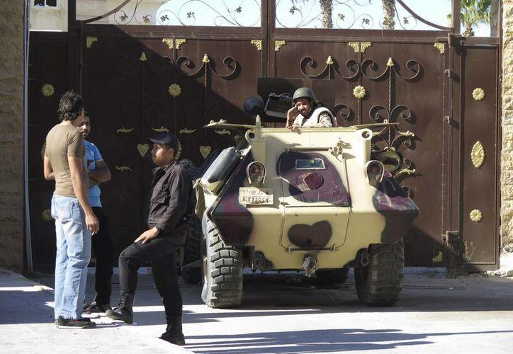En la imagen, un vehículo del Ejército egipcio custodia la entrada principal de la sede de la Gobernación de la provincia del Norte del Sinaí, en la ciudad de Al Arish.  Insurgentes islamistas lanzaron hoy ataques simultáneos  con 50 fallecidos. (EFE/Archivo)