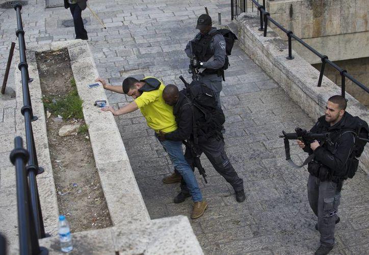 Un policía fronterizo israelí registra a un palestino en la Puerta de Damasco en la Ciudad Vieja de Jerusalén, Israel. (EFE)