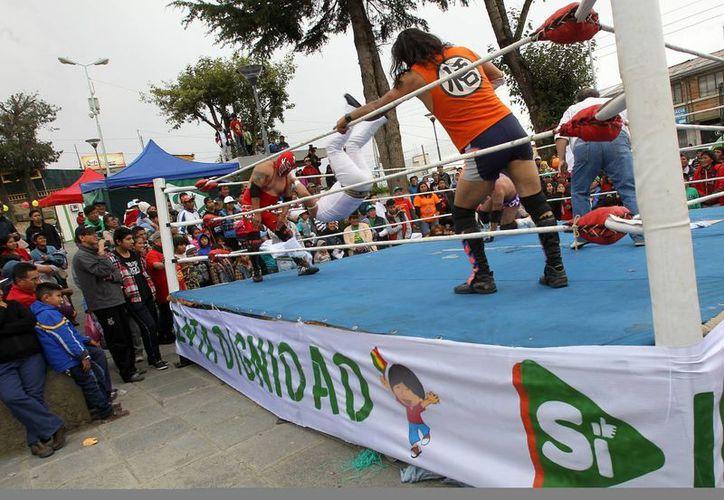 """El luchador Lucian (d) defendiendo el """"Sí"""" a la reforma constitucional boliviana, que se votará en un referendo en febrero, se enfrenta al luchador Chico Hawai (c) quien representa el """"No"""", en un evento organizado en la plaza del barrio Villa Armonía, La Paz. (EFE)"""