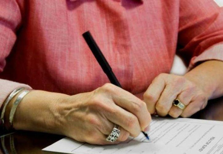 El testamento es atemporal y se refiere a los bienes, derechos, acciones y posesiones del testador al momento de su muerte. Imagen de una mujer al momento de firmar este documento. (Archivo/Agencias)