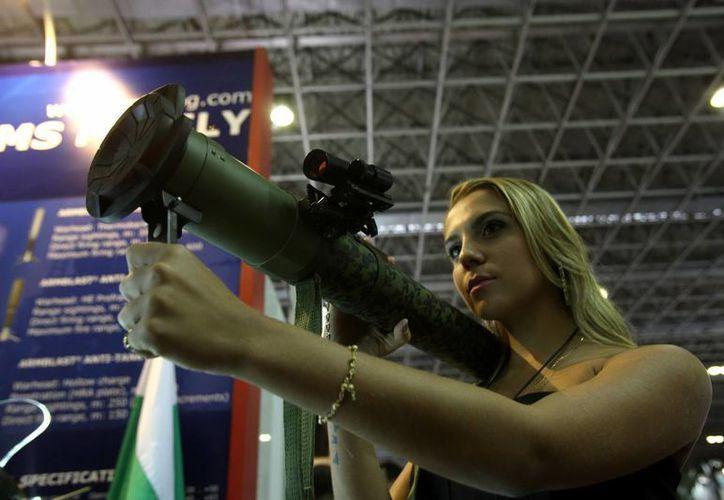 Una mujer observa un arma durante la feria internacional de armamento LAAD Defence & Security en la ciudad de Río de Janeiro. (EFE)