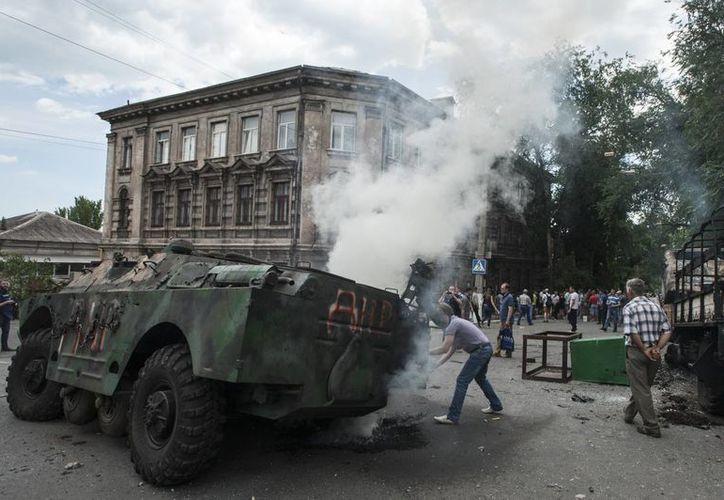 Ciudadanos se reúnen alrededor de un vehículo militar quemado durante el enfrentamiento entre las tropas ucranianas y prorrusos en Mariupol. (Agencias)