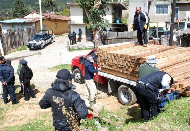 En esta imagen del 13 de noviembre de 2013, agentes de seguridad y de la Profepa decomisan madera en un aserradero del Estado de México, por no contar con el permiso. (Foto: Archivo/Notimex)