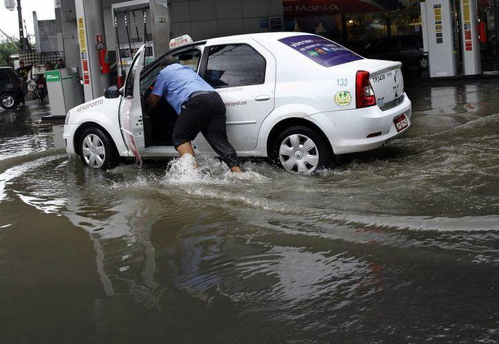 Un hombre empuja su vehículo en una calle inundada debido a las fuertes lluvias que han provocado numerosos problemas de tráfico en la ciudad de Recife, Brasil. (EFE)