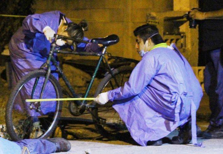 Peritos investigadores de la FGE toman pruebas en la escena del crimen. El joven fue atacado por tres sujetos cuando manejaba su bicicleta. (Milenio Novedades)